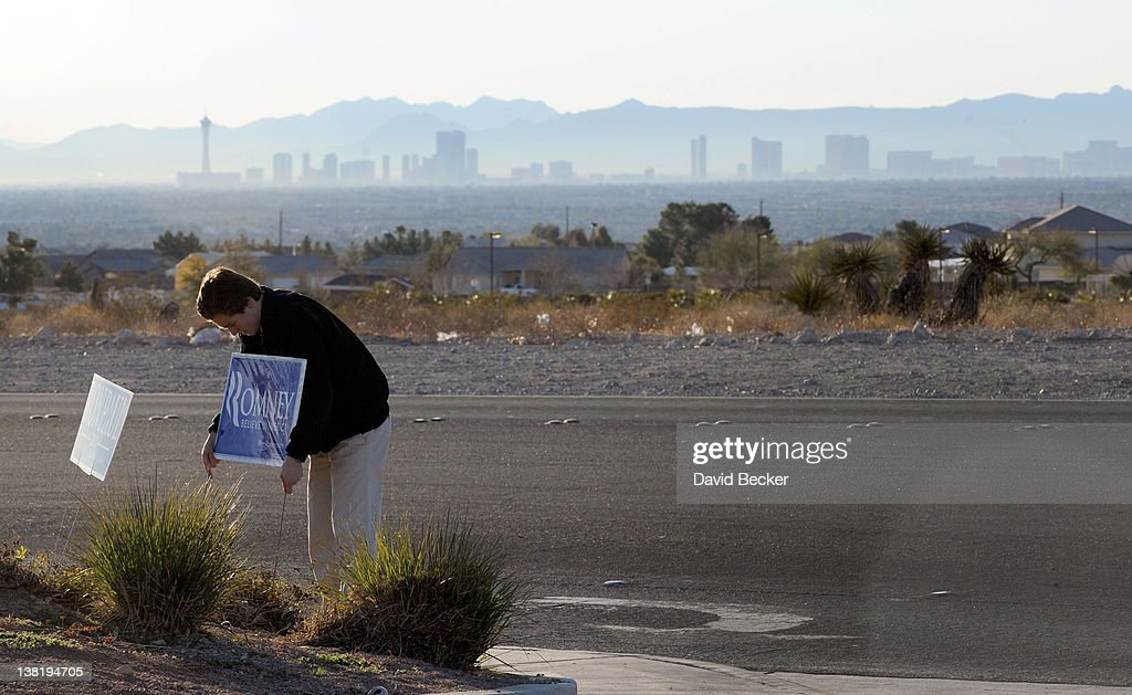 Volunteer Phil Soelberg sets up a political sign for Republican presidential candidate, former Massachusetts Gov. Mitt Romney at a caucus site at Centennial High School on February 4, 2012 in Las Vegas, Nevada. Polls are open as Nevada Republican voters make their picks in the presidential race in today's caucus.