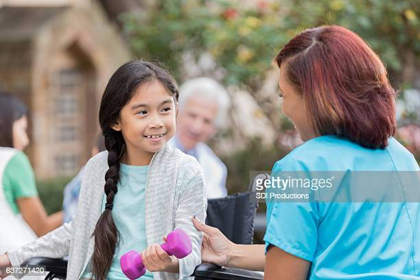 Volunteer physical therapist helps young girl at free clinic