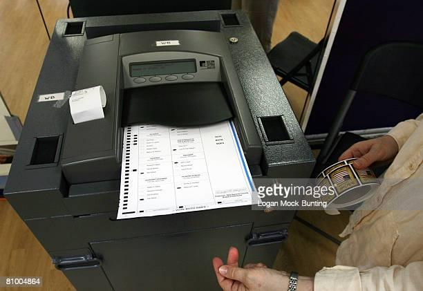 A volunteer places ballot into the collection machine at a polling station May 6 2008 in Wrightsville Beach North Carolina Democratic presidential...