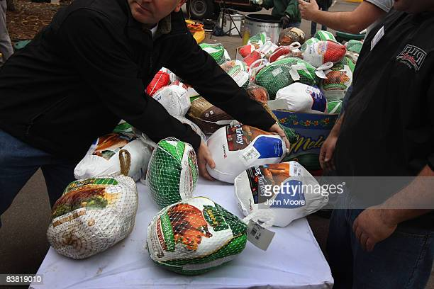 A volunteer prepares to give a turkey to a needy family at the annual Thanksgiving Banquet in a Box distribution November 25 2008 in Denver Colorado...