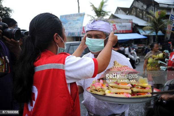 A volunteer puts a mask on a man due to ash in the air from Mt Agung volcano at a traditional market in the Rendang subdistrict of Karangasem Regency...