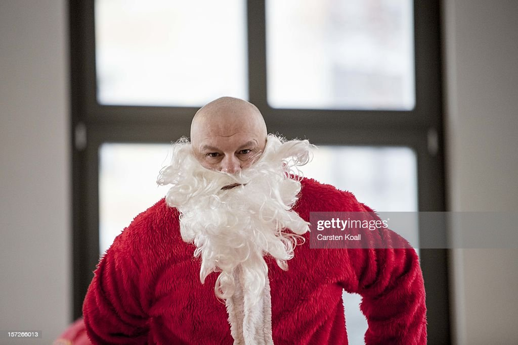 A volunteer puts on his costume as students dressed as Santas gather for their annual pre-Christmas gathering at the cafeteria of the Studentenwerk Nord student support service on December 1, 2012 in Berlin, Germany. The students, mostly from Berlin Technical University (Technische Universitaet Berlin), have completed a Santa workshop and will visit company parties in December and families on Christmas Eve as a way to make a little money to help fund their studies.