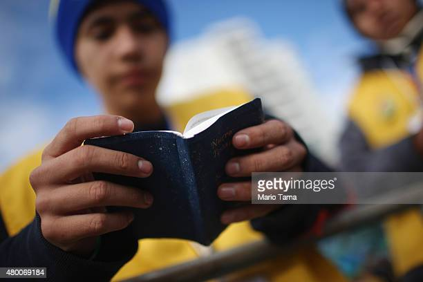 A volunteer reads a copy of the New Testament before the start of Pope Francis' openair Mass on July 9 2015 in Santa Cruz Bolivia Pope Francis will...