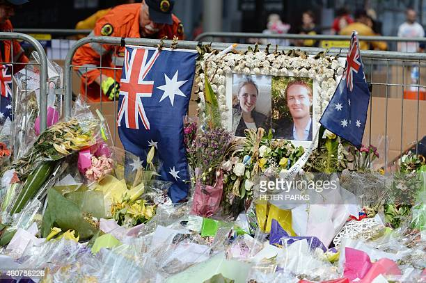 A volunteer removes flowers next to a photo showing Katrina Dawson and Tori Johnson at a memorial site outside the Lindt cafe in Sydney on December...