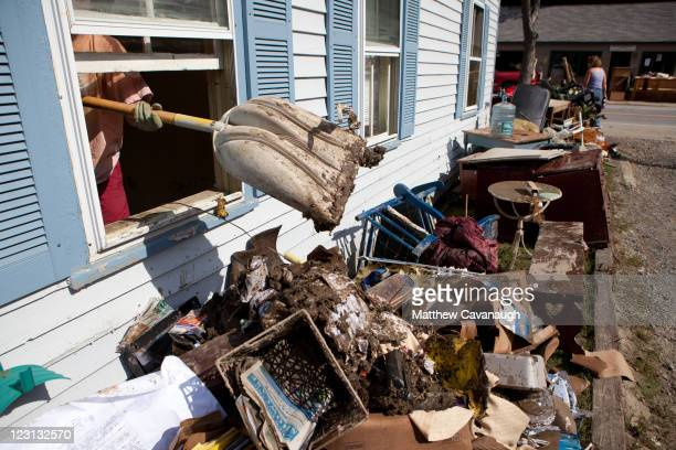 A volunteer removes mud and debris from a real estate office that was flooded in tropical storm Irene on West Main Street on August 31 2011 in...