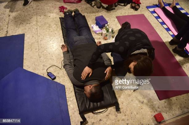 Volunteer rescuers working on the ruins of a building toppled by a 71magnitude quake that struck central Mexico almost a week ago get massages from...