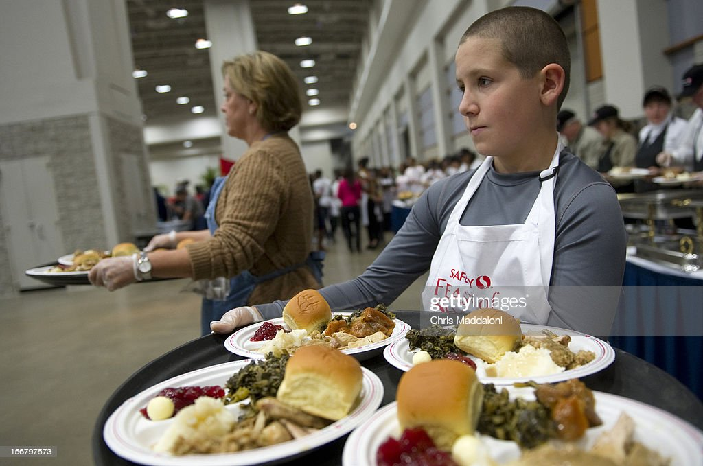 Volunteer Richard Miller, from Waldorf, Md., serves plates at the 13th annual Safeway Feast of Sharing at the Washington Convention Center. More than 5000 people were expected for the free Thanksgiving meal, job and health fair.