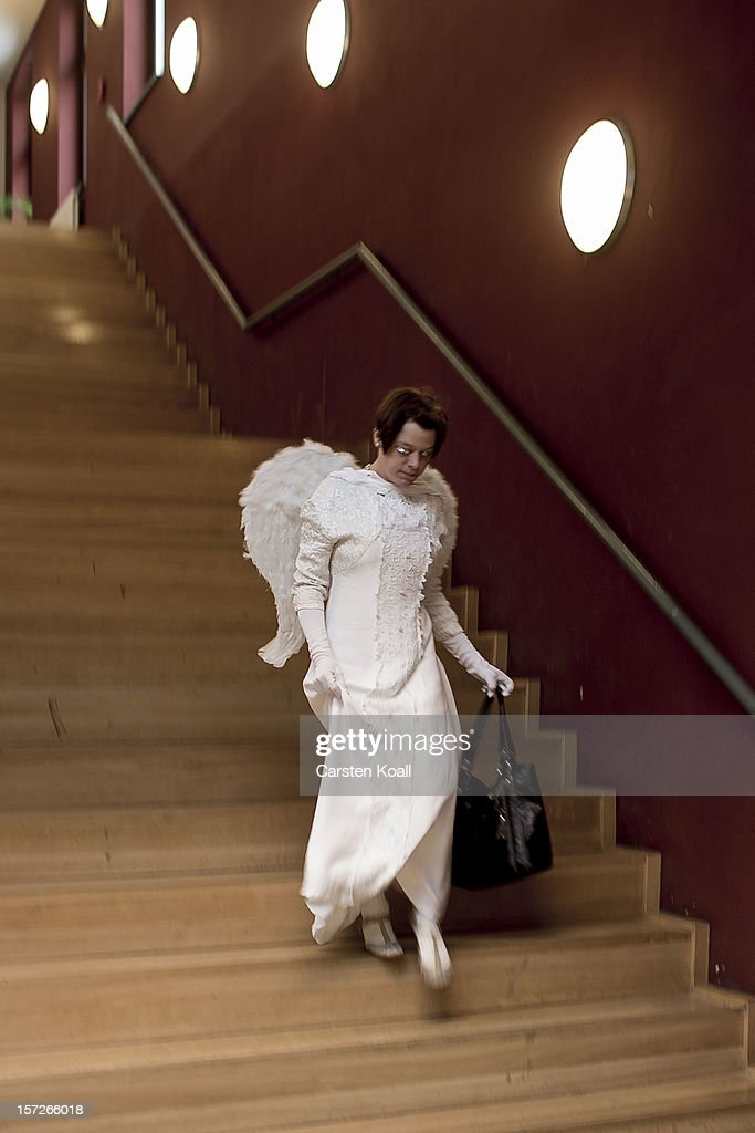 A volunteer runs down a staircase as students dressed as Santas and angels gather for their annual, pre-Christmas gathering at the cafeteria of the Studentenwerk Nord student support service on December 1, 2012 in Berlin, Germany. The students, mostly from Berlin Technical University (Technische Universitaet Berlin), have completed a Santa workshop and will visit company parties in December and families on Christmas Eve as a way to make a little money to help fund their studies.