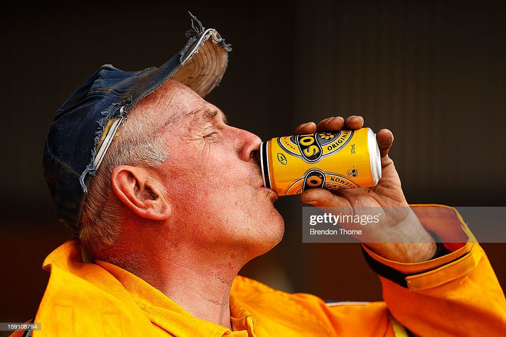A volunteer Rural Fire Service member from Bungendore RFS cools down by drinking a can of soft drink on January 8, 2013 in Bungendore, Australia. NSW was declared a total fire ban with the Illawarra, Shoalhaven and Southern Ranges regions placed on 'Catastrophic' alert.