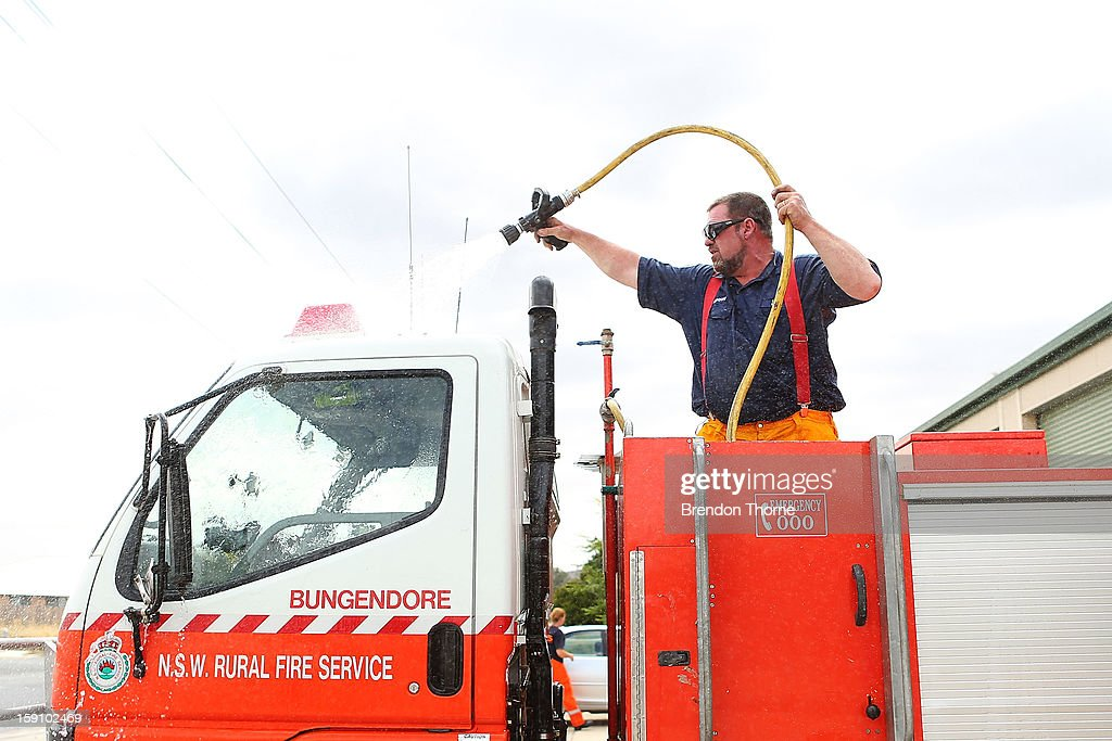 A volunteer Rural Fire Service member from Bungendore RFS washes down a emergency service vehicle on January 8, 2013 in Bungendore, Australia. NSW was declared a total fire ban with the Illawarra, Shoalhaven and Southern Ranges regions placed on 'Catastrophic' alert.