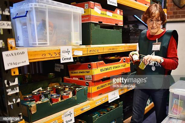 A volunteer selects food for a visitor's order at a foodbank charity in west London on December 23 2014 Food bank use in Britain is growing rapidly...