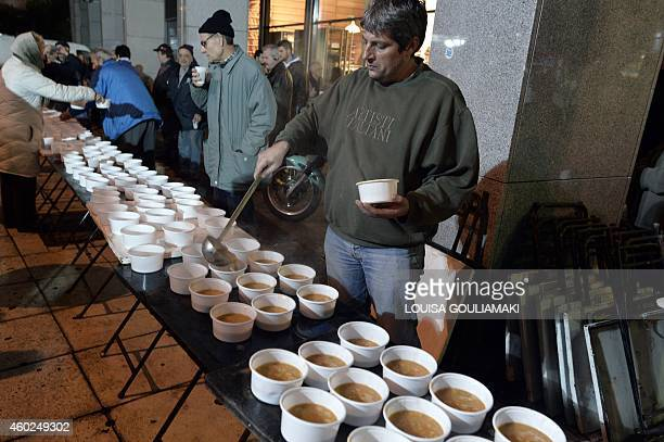 A Volunteer serves a hot bean soup outside the finance ministry in Athens late on December 10 for pensioners participating in a nightlong protest...