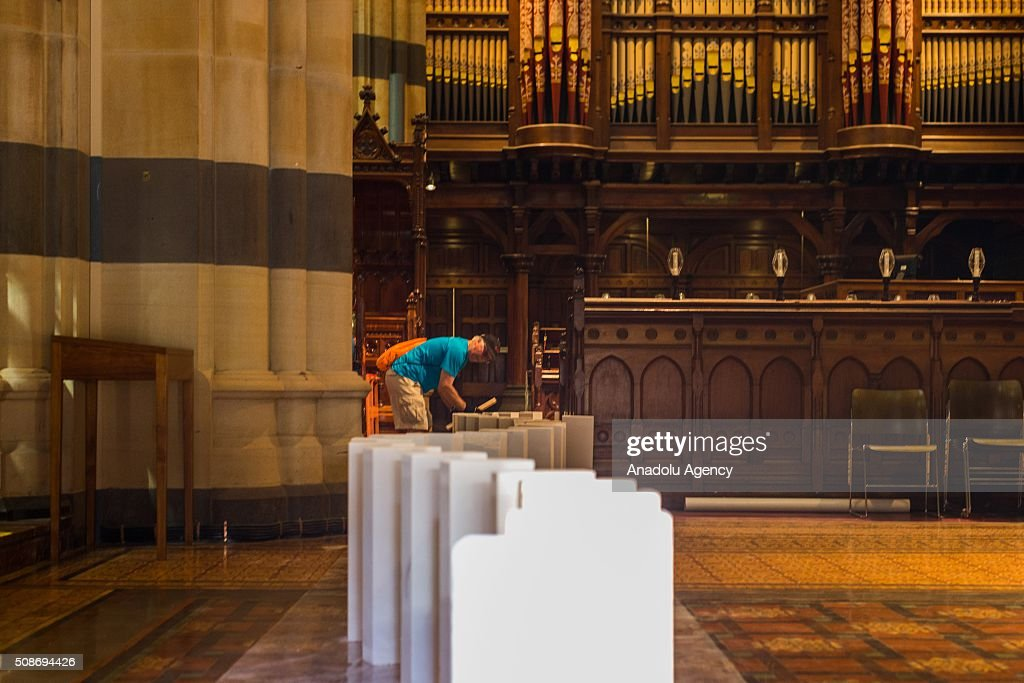 A volunteer sets up dominoes inside the St Pauls Cathedral during the Arts Centre Melbournes Dominoes arts project in Melbourne, Australia February 6, 2016. More than 7000 giant dominoes snaked through Melbourne city over 2km.