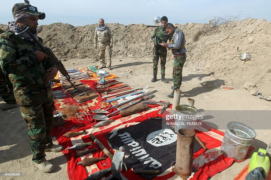 Volunteer Shiite fighters who support the government forces in the combat against the Islamic State group check weapons allegedly belonging to IS...