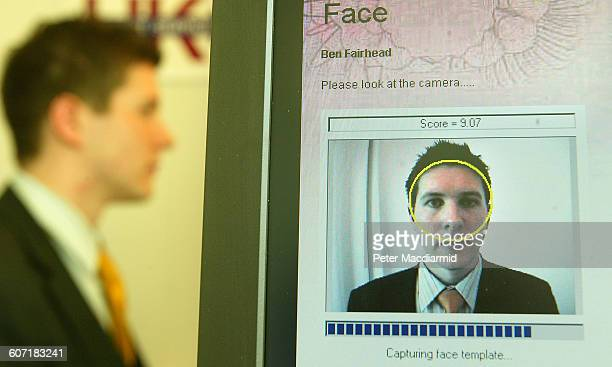 A volunteer sits as his face is scanned for a biometrics enrolment card in British Passport Office London England April 24 2004