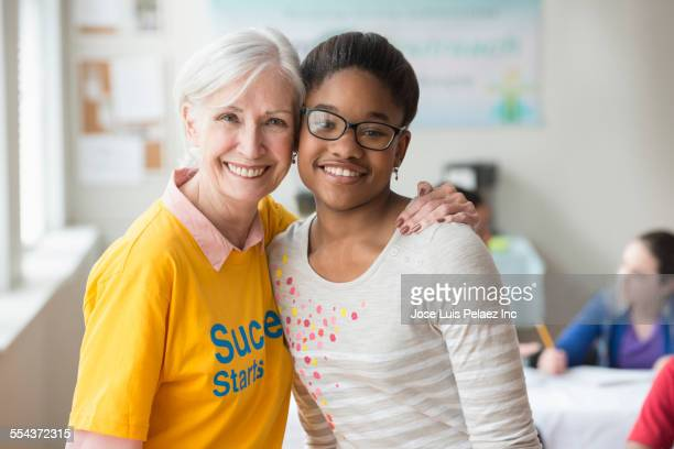 Volunteer smiling with student in classroom