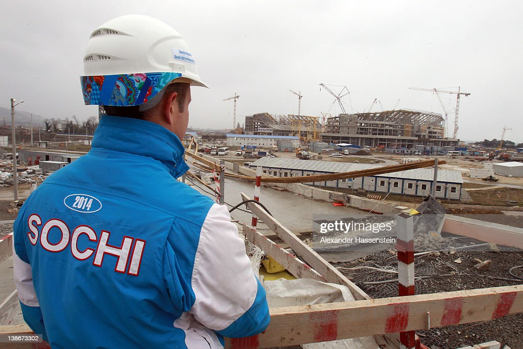 A volunteer stands in front of the construction site of the Olympic stadium 'Fisht' on February 10, 2012 in Sochi, Russia. The 'Fisht' will host the opening and the closing ceremonies of the 2014 Olympic and Paralympic Winter Games in the Black Sea resort of Sochi. The stadium with a capacity of 40,000 spectators is expected to be completed in May 2013 and will host football matches including the 2018 FIFA World Cup following the Games.