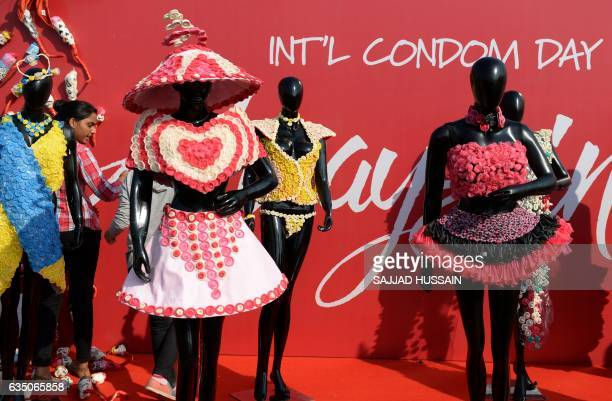 A volunteer stands near mannequin wearing dresses decorated with condoms during an event to mark International Condom Day in New Delhi on February 13...