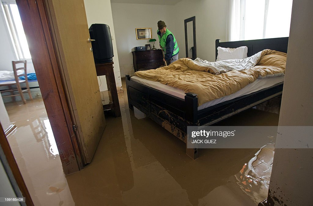 A volunteer sweeps murky water from a flooded house in Beit Hefer near the Mediterranean coastal city of Netanya, north of Tel Aviv, on January 9, 2013, after heavy rains overnight. Israel and the Palestinian territories have been lashed by heavy rain and high winds since January 6, which has caused flooding across the region. AFP PHOTO / JACK GUEZ