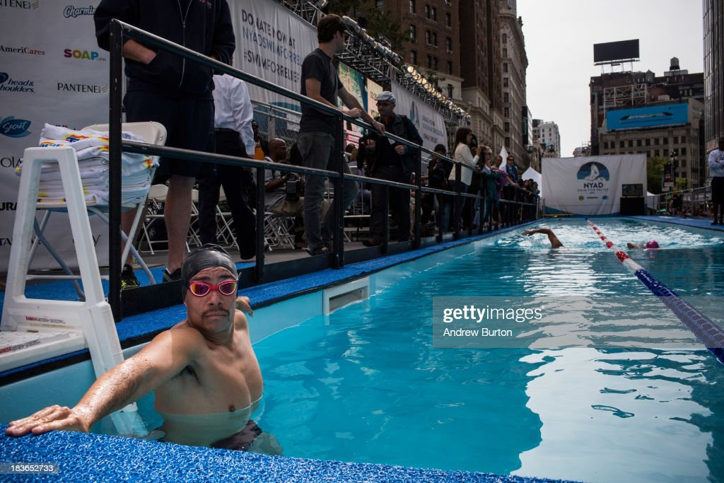 A volunteer swim partner from the Fire Department of New York (FDNY) waits for distance swimmer Diana Nyad (R) during her attempt to swim for 48 hours straight in a constructed 40-meter pool in Herald Square, to support victims of Hurricane Sandy on October 8, 2013 in New York City. In August 2013 Nyad, age 64, swam non-stop from Florida to Cuba without a shark cage, a distance of approximately 110 miles, in approximately 53 hours. Nyad will swim with partners throughout the 48 hour challenge, and will be visited by various athletes and celebrities, too.
