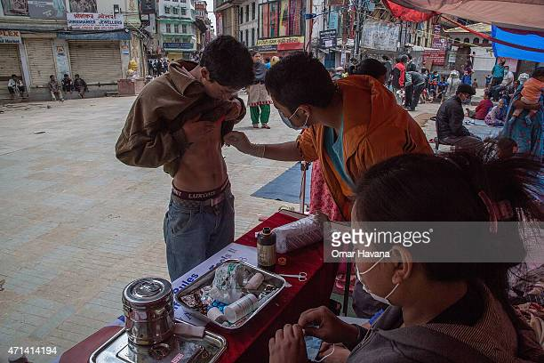 A volunteer treats a wound on a young man in one the temporary street shelters near Basantapur Durbar Square on April 28 2015 in Kathmandu Nepal A...