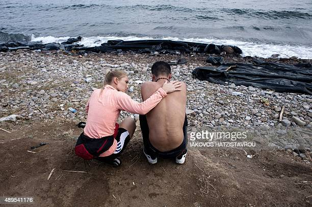 A volunteer tries to console a refugee on Sykamia beach west of the port of Mytilene on the Greek island of Lesbos after crossing the Aegean sea from...