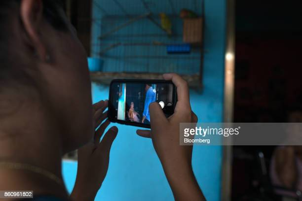 A volunteer uses a smartphone to take a photograph of Jose Manuel Olivares opposition coalition governor candidate for Vargas State with a resident...