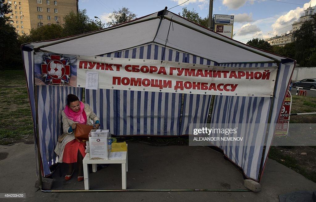 A volunteer waits for people to donate money or goods in central Moscow on August 26, 2014. Banner reads : 'A point of collection of humanitarian aid to Donbas'.