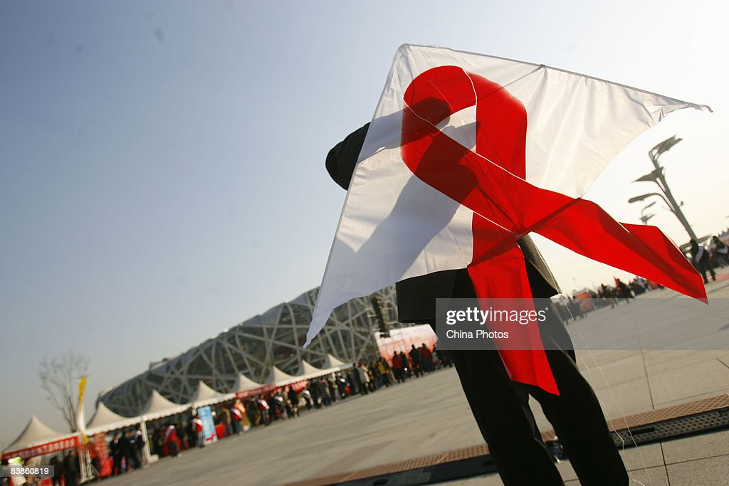 A volunteer waits to fly a kite decorated with a red ribbon during an AIDS awareness promotion at the National Stadium to mark the upcoming World...