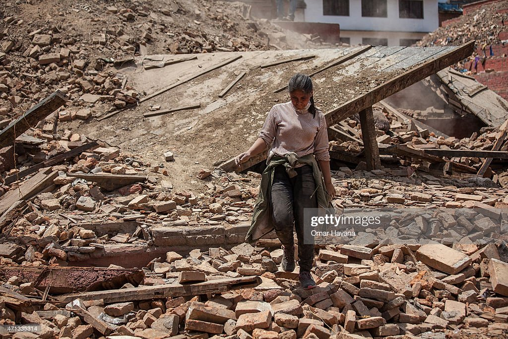 A volunteer walks on top of the debris of a collapsed temple at Basantapur Durbar Square on April 27 2015 in Kathmandu Nepal A major 78 earthquake...