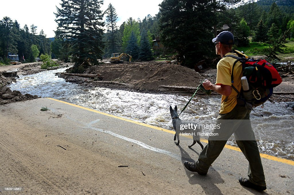 A volunteer who wanted to go only by the name of Ken walks with his dog Bandit along Colorado Road 43 near Glen Haven, CO on his way back to where he is sleeping after a day of helping Glen Haven firefighters begin the clean up of their town on September 17, 2013. The small mountain town of Glen Haven north east of Estes Park has been wiped out by the recent and massive flooding.