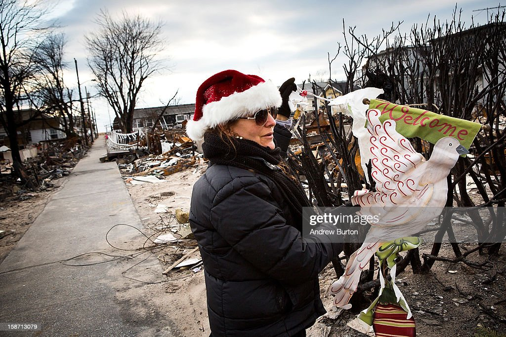 A volunteer who would only identify herself as 'Nancy' hangs an ornament on the remains of a dead bush December 25, 2012 in the Breezy Point neighborhood of the Queens borough of New York City. Residents are still struggling to recover from a massive fire that destroyed over 100 homes during Superstorm Sandy.