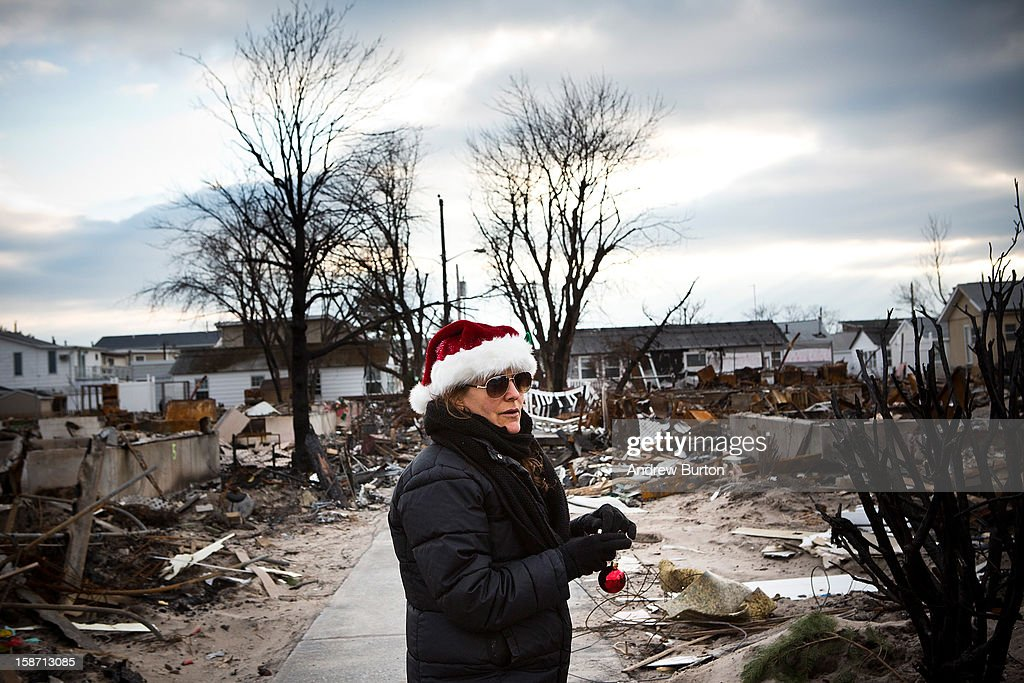 A volunteer who would only identify herself as 'Nancy' helps decorate a Christmas Tree December 25, 2012 in the Breezy Point neighborhood of the Queens borough of New York City. Residents are still struggling to recover from a massive fire that destroyed over 100 homes during Superstorm Sandy.