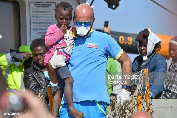 A volunteer with a child during the landing of migrants by Turkish cargo ship Kaptan Hilmi III in port of Corigliano Calabria southern Italy The...