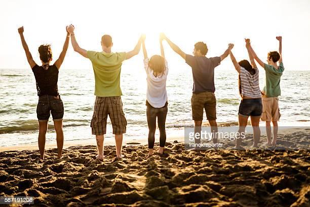 Voluntário com braços levantado ao pôr do sol