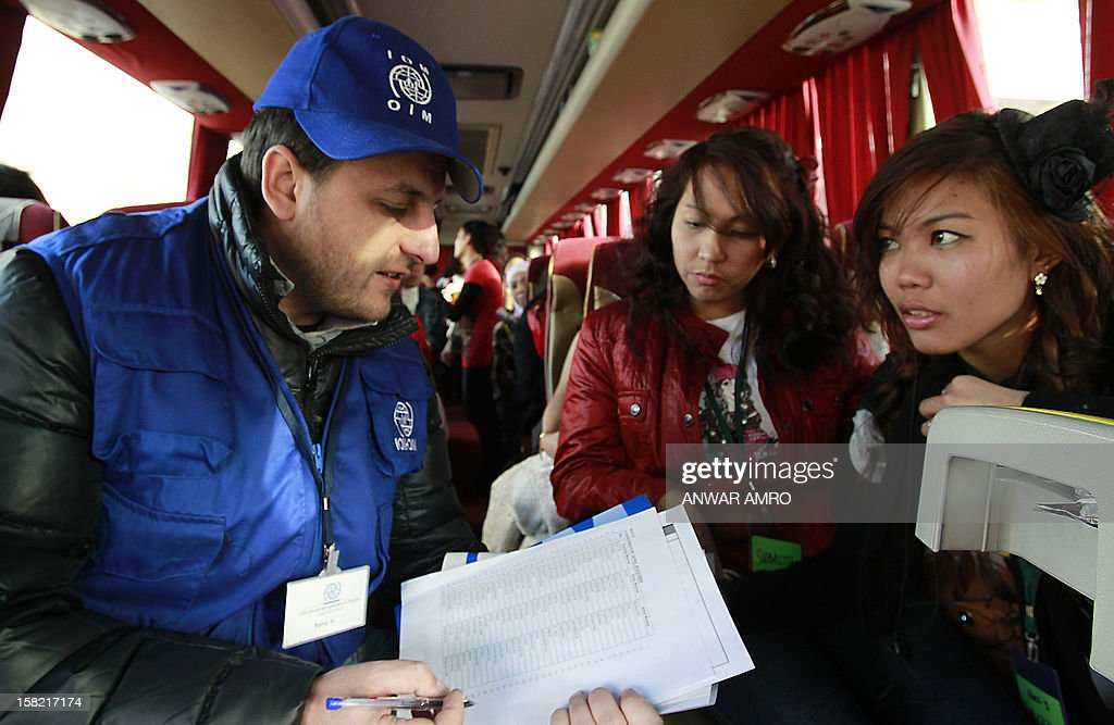 A volunteer with International Organisation for Migration (IOM) checks the names of two Filipino nationals as Asian women who were working in Syria are seen inside a bus after they left the war-torn country with the help of IOM, on December 11, 2012 at the Lebanese border with Syria. The workers headed to Beirut International Airport from where they flew to their respective countries. AFP PHOTO/ANWAR AMRO