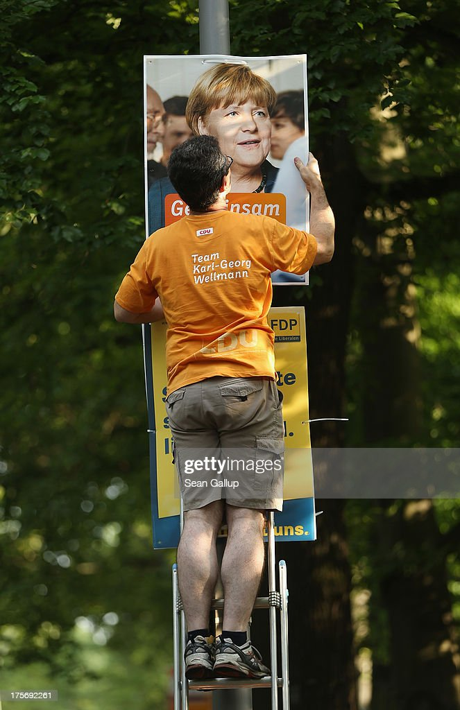 A volunteer with the German Christian Democrats (CDU) hangs a CDU election campaign poster that shows German Chancellor and CDU Chairwoman Angela Merkel on a lamppost on August 6, 2013 in Berlin, Germany. Germany is scheduled to hold federal elections on September 22 and so far current Chancellor Angela Merkel and her party, the German Christian Democrats (CDU), have a strong lead over the opposition.