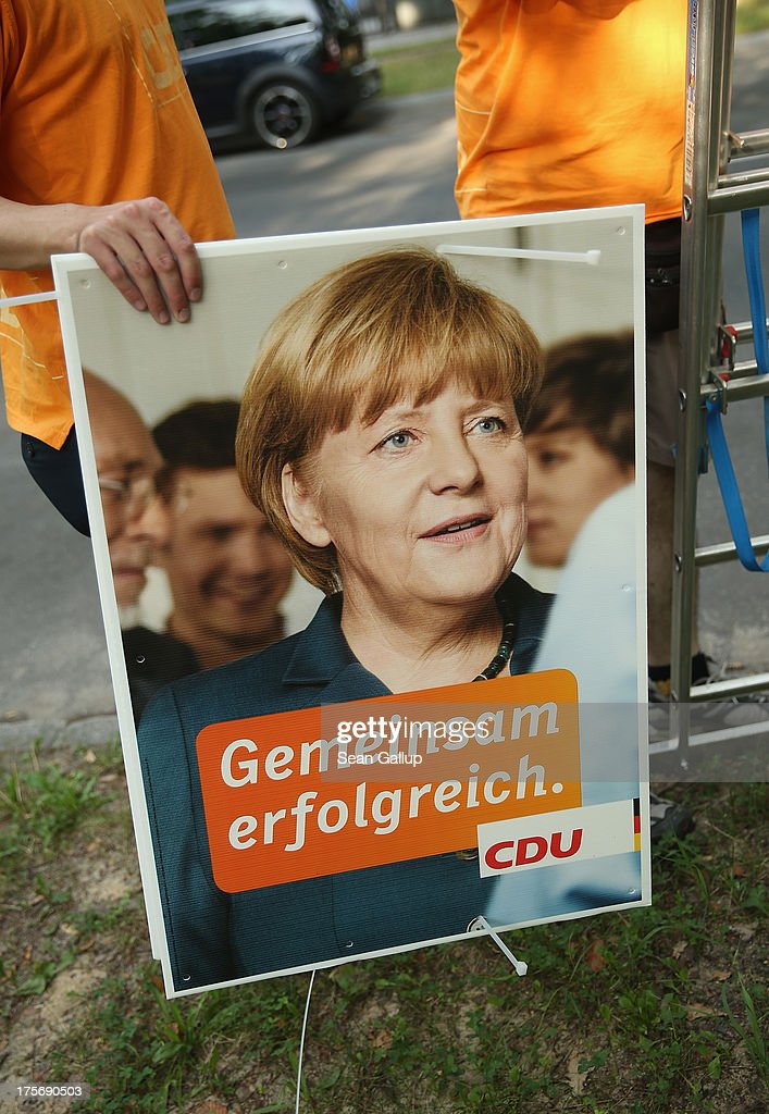 A volunteer with the German Christian Democrats (CDU) prepares to hang a CDU election campaign poster that shows German Chancellor and CDU Chairwoman Angela Merkel on August 6, 2013 in Berlin, Germany. Germany is scheduled to hold federal elections on September 22 and so far current Chancellor Angela Merkel and her party, the German Christian Democrats (CDU), have a strong lead over the opposition.