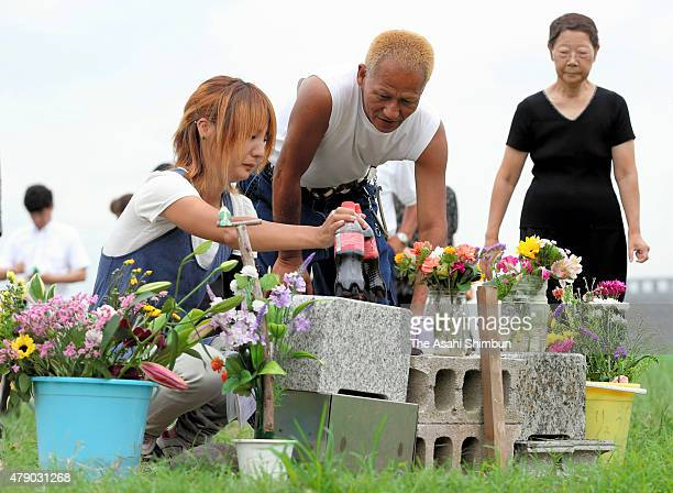 Volunteer workers remove a makeshift altar for killed 13yearold Ryota Uemura at Tamagawa River on June 30 2015 in Kawasaki Kanagawa Japan Three...