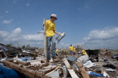 Volunteer Zachary Farmer of Independence Kansas picks up rubble while clearing the remains of a home on June 18 in Joplin Missouri Farmer travelled...