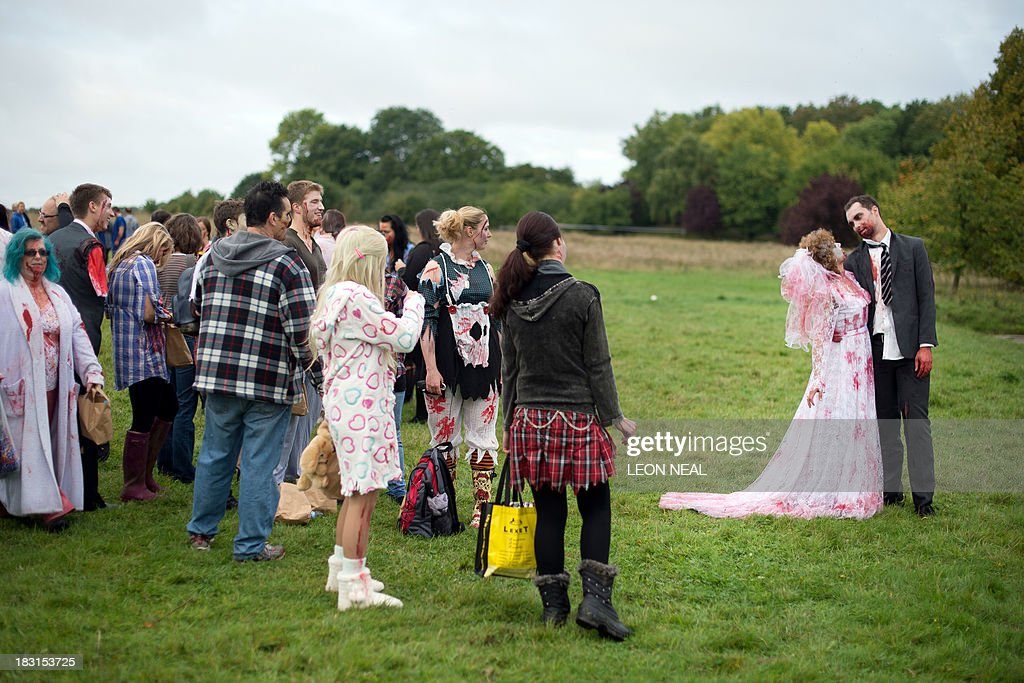 A volunteer zombie bride and groom prepare to take part in one of Britain's biggest horror events, the 'Zombie Evacuation Race' at Carver Barracks near Saffron Walden, England, on October 5, 2013. The race sees thousands of participants attempt to complete a gruelling 5 kilometre cross-country run, while evading 'zombies', intent on snatching the three life-line strips hanging from every runner's waist. Those who manage to get through with any strips remaining are named as survivors while those without take home an 'infected' badge. AFP PHOTO/Leon Neal