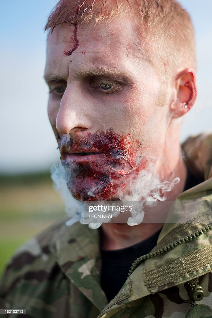 A volunteer 'zombie' smokes a cigarette before taking part in one of Britain's biggest horror events, the 'Zombie Evacuation Race' at Carver Barracks near Saffron Walden, England, on October 5, 2013. The race sees thousands of participants attempt to complete a gruelling 5 kilometre cross-country run, while evading 'zombies', intent on snatching the three life-line strips hanging from every runner's waist. Those who manage to get through with any strips remaining are named as survivors while those without take home an 'infected' badge. AFP PHOTO/Leon Neal