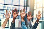 Cropped shot of a group of unrecognizable businesspeople raising their hands