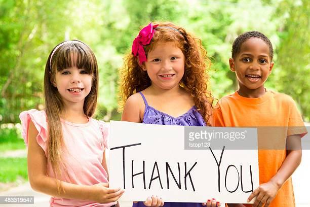 Ehrenamtliche Arbeit: Drei hübsche Kinder hält ein Danke-Schild. Nächstenliebe.