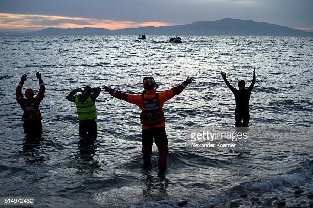 Volunteers and Lifeguards direct an inflatable boat with refugees crossing the sea from Turkey to Lesbos some 5 kilometres south of the capital of...
