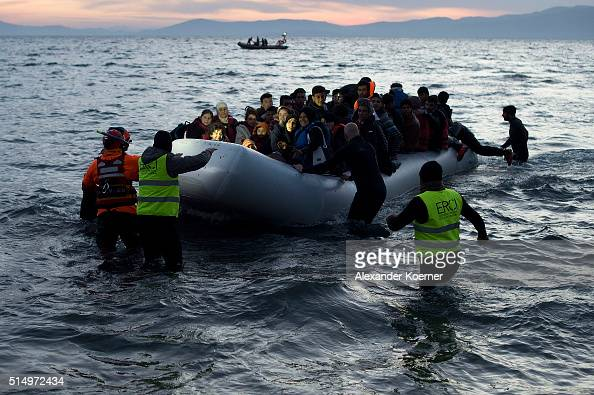 Volunteers and Lifeguards help an inflatable boat with refugees crossing the sea from Turkey to Lesbos some 5 kilometres south of the capital of the...