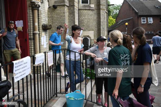 Volunteers and members of the public talk outside the Notting Hill methodist Chruch June 14 2017 in London England The Mayor of London Sadiq Khan has...