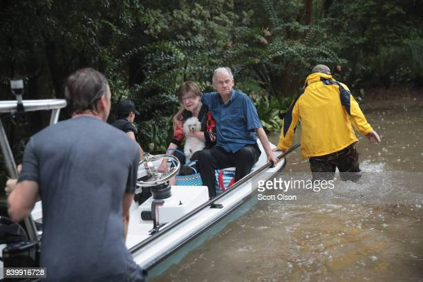Volunteers and officers from the neiborhood security patrol help to rescue residents in the upscale River Oaks neighborhood after it was inundated...