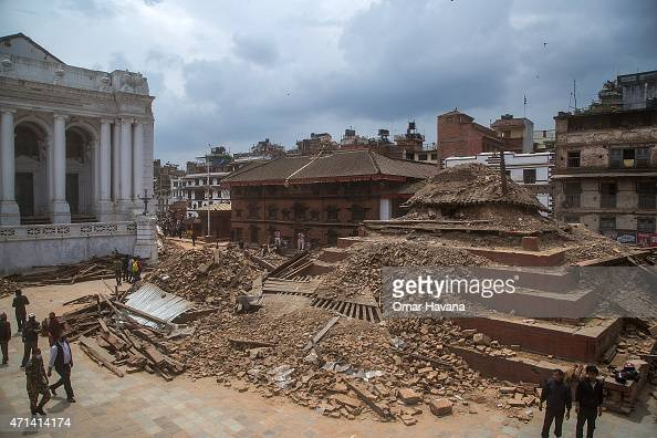 Volunteers and quake emergency team members walk around one of the collapsed UNESCO World Heritage site temples in Basantapur Durbar Square on April...