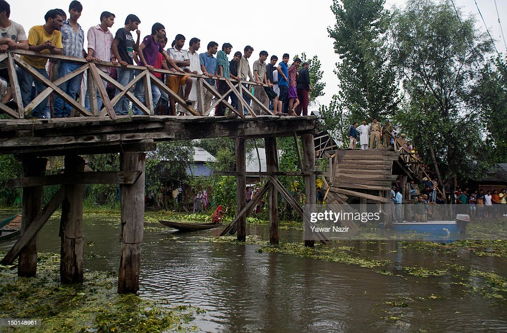 Volunteers and rescuers search for survivors in the water after a footbridgecollapsed into the water on August 11, 2012 in Srinagar, the summer capital of Indian administered Kashmir, India. According to witnesses and locals many people were injured some of them critically after an old makeshift foot bridge partially crumbled down due to overweight, in the interiors of Dal Lake .